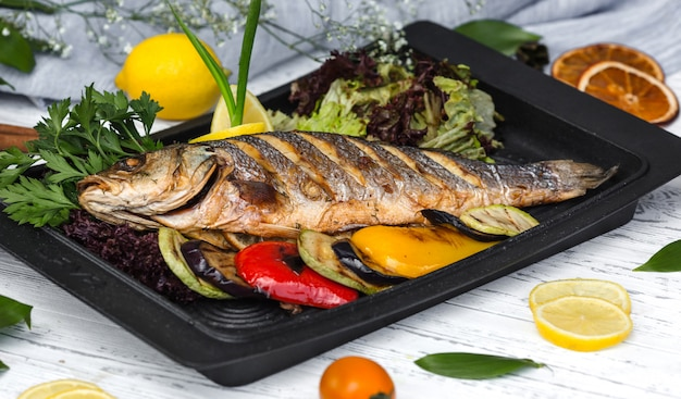 Roasted fish garnished with lemon slices served with vegetables