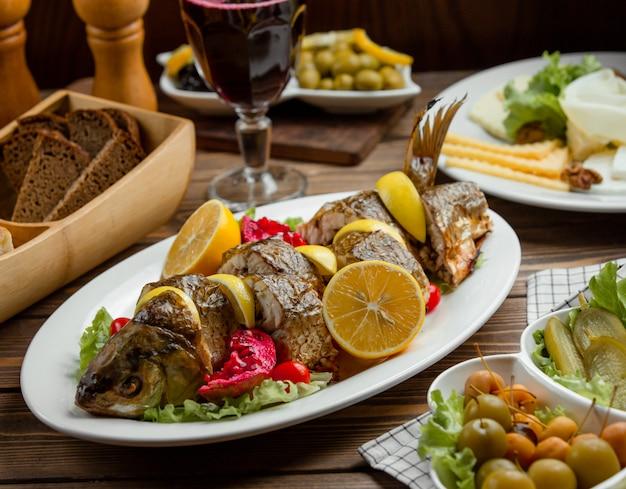 Pesce arrosto servito con limoni e melograno con piatto di formaggi
