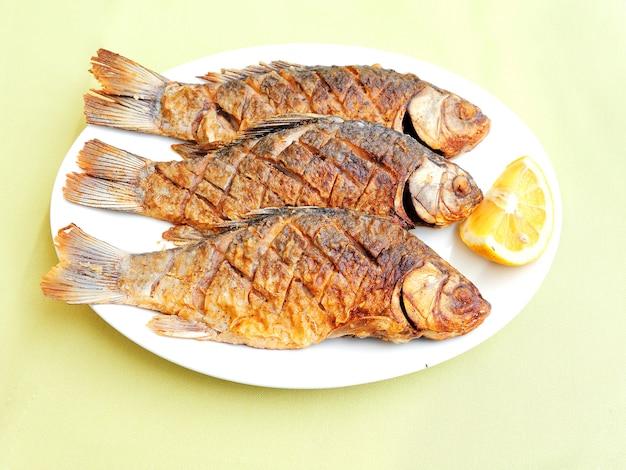 皿にレモンとロースト魚