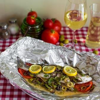 오븐에서 알루미늄 호일로 요리 한 소스와 야채를 곁들인 구운 생선