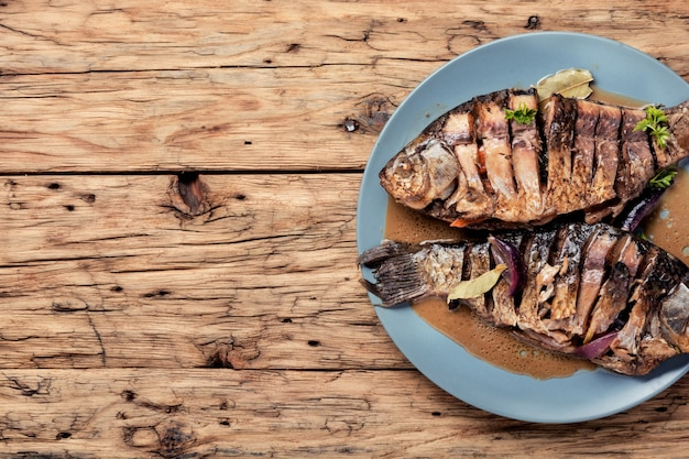 Roasted fish on wooden background