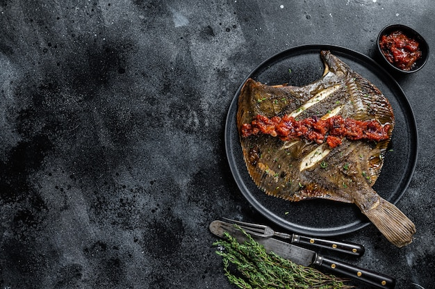 Roasted flatfish or flounder in a tomato sauce. black background. top view. copy space.