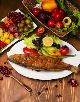 Roasted fried whole fish with grilled vegetables and lettuce. in white plate decorated with turshu on wooden table