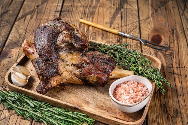木製のカッティングトレイで焼いた山羊の脚肉。木製のテーブル。上面図。