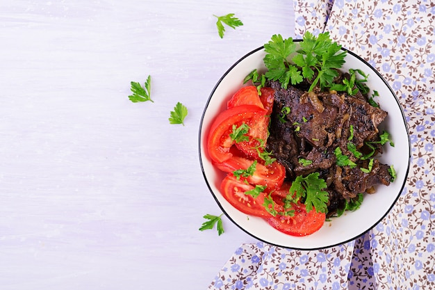 Roasted or grilled beef liver with onion and tomatoes salad, middle eastern cuisine, top view