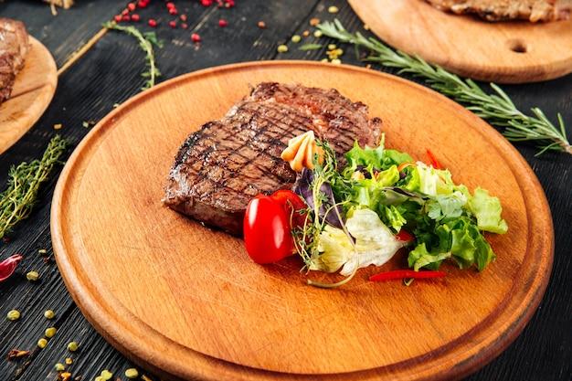 Roasted grilled beef meat steak on wooden board
