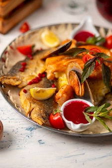 Roasted grilled fish and seafood served with herbs, lemon and dip red tomato sauce.
