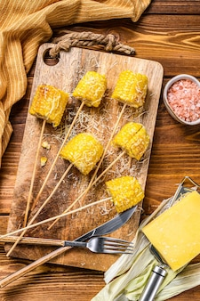 Roasted or grilled sweet corn cobs with garlic and butter. wooden background.