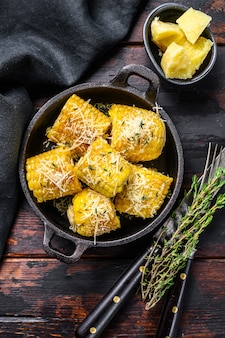 Roasted or grilled sweet corn cobs with garlic and butter