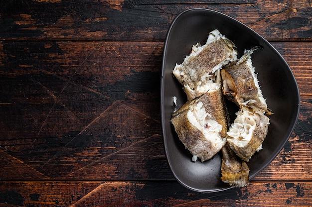 Жареный хек белая рыба в тарелке