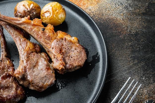 오래 된 어두운 시골 풍 테이블에 접시에 마늘과 허브 세트로 구운 양고기 커틀릿 갈비