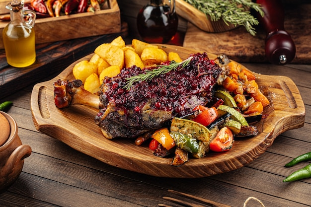 Roasted lamb knuckle with lingonberry sauce and vegetables
