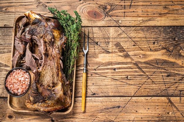Жареная баранина ягненка нарезка плечевого мяса в деревянном подносе с вилкой для мяса. деревянный фон. вид сверху. скопируйте пространство.