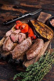 나무 커팅 보드에 구운 양고기 안심 등심 고기 스테이크. 어두운 나무 배경입니다. 평면도.