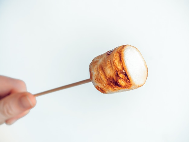 Roasted marshmallows on a skewer in female hand on white