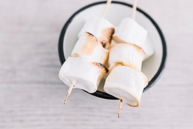 Marshmallow arrostiti su bastoncini di legno