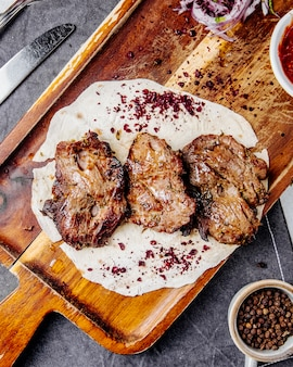 Roasted meat pieces on a wooden board