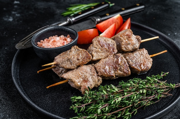 Roasted meat skewers shish kebab and vegetables on a plate. black background. top view.