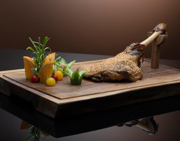 暗い背景の木製トレイにゴマとロースト肉