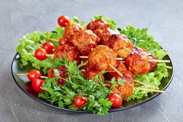 Roasted meatballs on skewers with fresh tomatoes on a bed of lettuce leaves, horizontal view from abov
