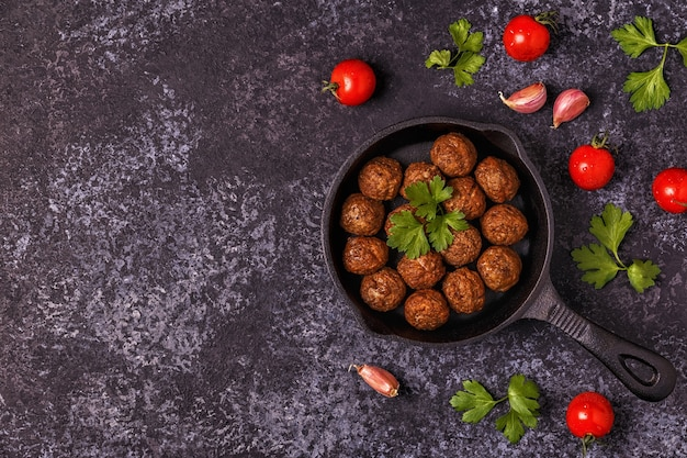 Roasted meatballs with tomatoes, garlic and parsley