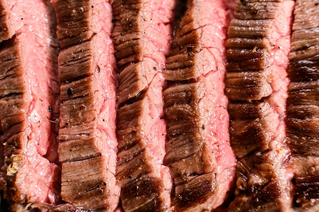 Roasted medium rare sliced flank beef steak. black background. top view