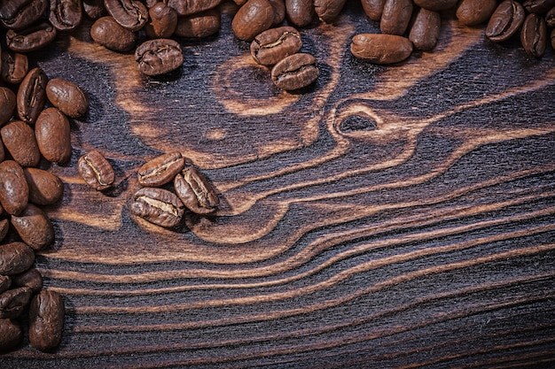 Roasted natural coffee beans on vintage wooden board