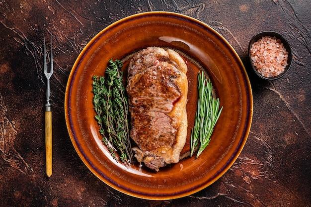 Roasted new york strip beef meat steak or striploin in a rustic plate