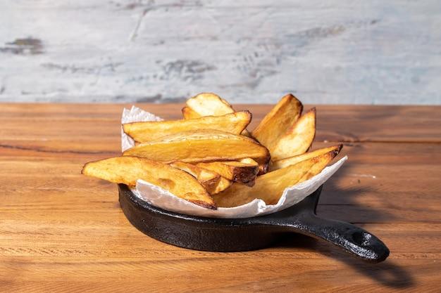 Жареный или запеченный картофель в черной сковороде на деревянном столе.
