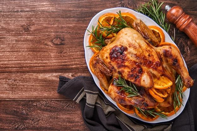 Жареный или запеченный целый цыпленок с розмарином и апельсинами, домашний для семейного обеда на коричневом каменном столе. вид сверху с копией пространства.