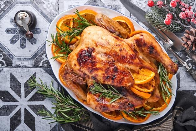 갈색 돌 테이블에서 가족 저녁 식사를 위해 홈메이드 로즈마리와 오렌지를 곁들인 구운 또는 구운 통닭. 복사 공간이 있는 상위 뷰입니다.
