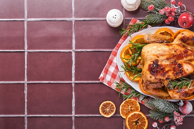Жареный или запеченный целый цыпленок с розмарином и апельсинами, домашний для традиционного рождественского семейного обеда на коричневом каменном столе. вид сверху с копией пространства.