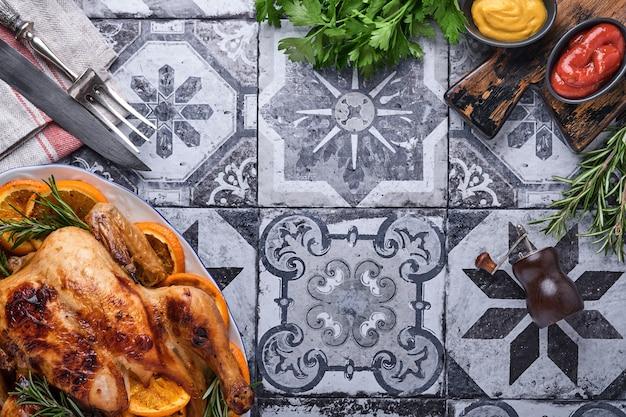 Жареный или запеченный цельный цыпленок с розмарином и апельсинами, домашний на рождественский традиционный семейный ужин на старом каменно-сером деревенском столе. вид сверху с копией пространства.