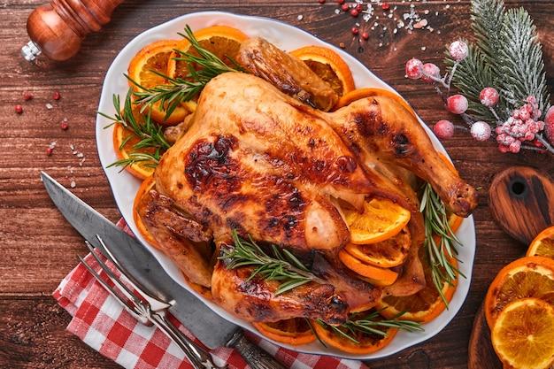 Жареный или запеченный цельный цыпленок с розмарином и апельсинами, домашний на рождественский традиционный семейный ужин на старом деревянном деревенском столе. вид сверху с копией пространства.
