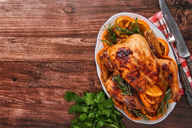 Жареный или запеченный весь цыпленок с розмарином и апельсинами, домашний на рождественский традиционный семейный ужин на старом деревянном деревенском столе. вид сверху с копией пространства.