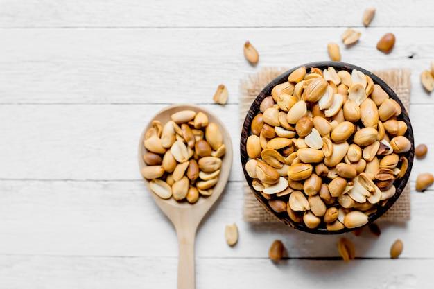 Жареный арахис помещают в деревянную миску.