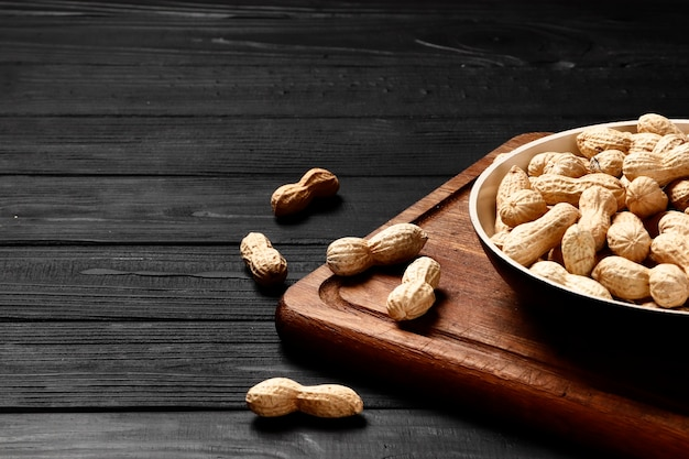 Roasted peanuts in a pan on a black wooden background. place for text. top view.