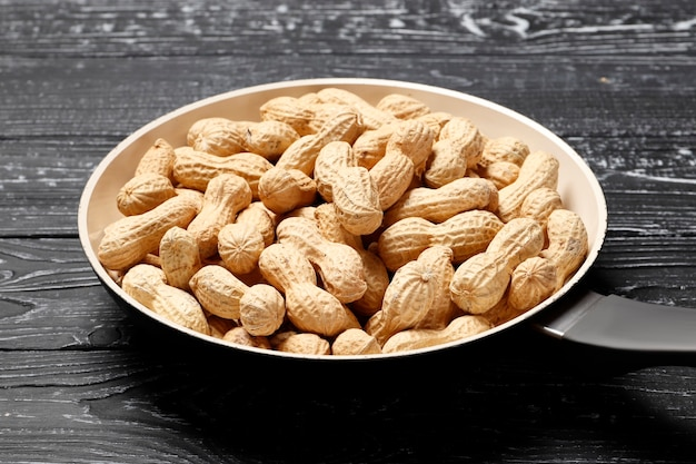 Roasted peanuts in a pan on a black wooden background