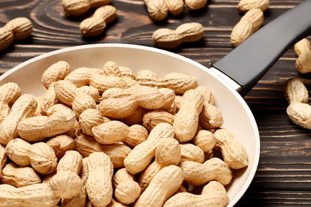 Roasted peanuts in a pan on a wooden background. place for text.