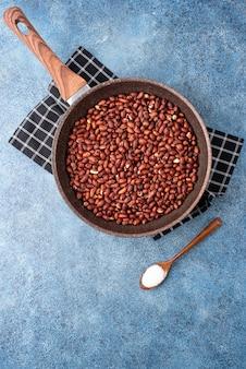 Арахис жареный с солью в кастрюле.