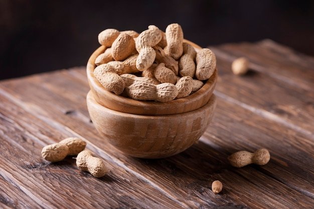 roasted peanuts in wooden bowl on dark background, selective focus image