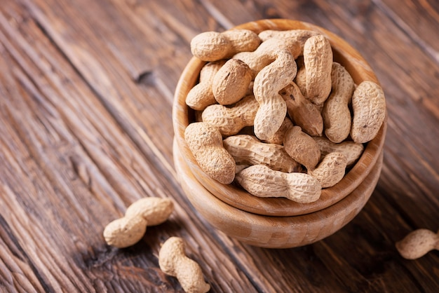 roasted peanuts in wooden bowl on dark, selective focus image