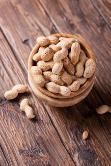 Roasted peanuts in wooden bowl on dark surface