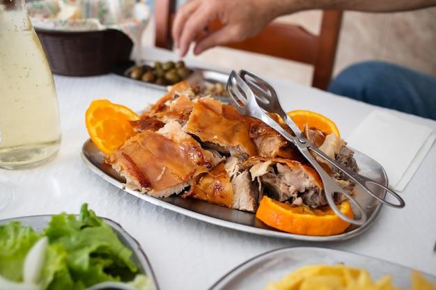 レストランの皿にオレンジ色のロースト豚の丸焼き