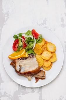 Жареный поросенок с картофельными чипсами и апельсином на белой тарелке
