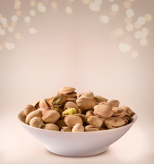 Roasted pistachio into a bowl on beige background.