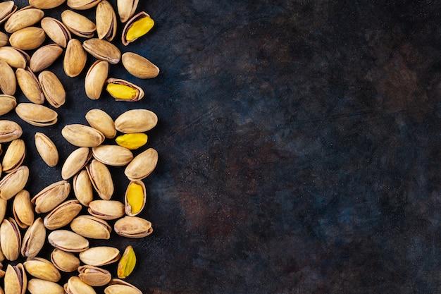 Жареные фисташки на темном фоне. фисташки - здоровая вегетарианская белковая питательная пища. здоровая закуска. скопируйте пространство. вид сверху