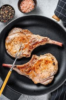 Жареный стейк из свиной отбивной на сковороде