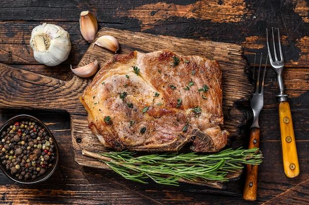Жареный стейк из свиной отбивной на разделочной доске