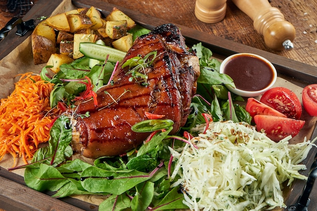 Жареная свиная рулька в пиве и мёде с помидорами, капустой и картофелем. традиционная немецкая пивная еда.